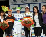The podium of the women's race. The riders flanked by the podium girls.