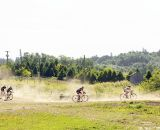Riders kick up dust as they pedal across the field. © Joe Sales