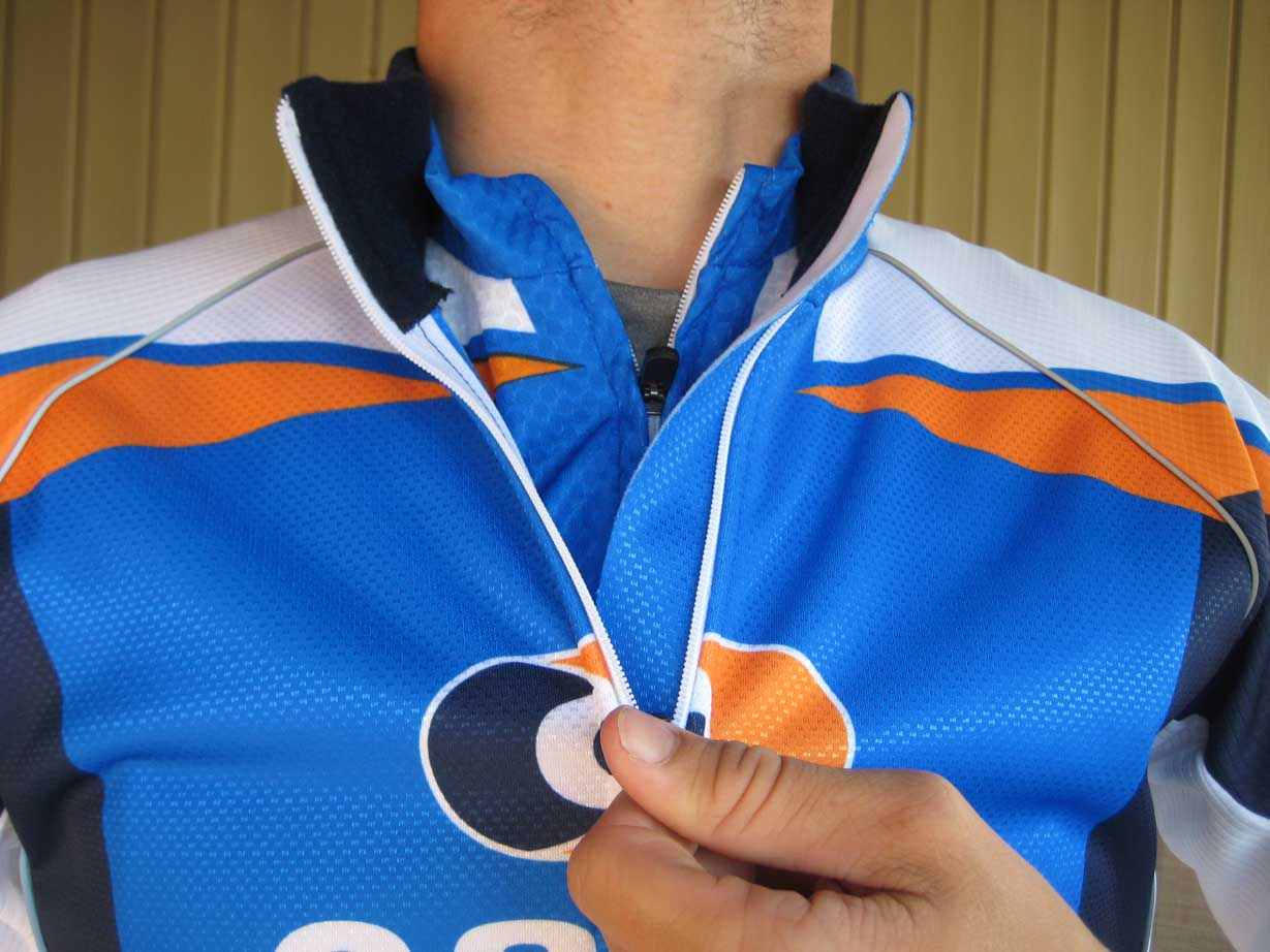 Layered with the short sleeve jersey, the wind jacket's zipper has a full length backing to keep the breeze from chilling your core.  The tall stand up fleece collar is nicely finished and keeps your neck toasty throughout your ride. by Kristie Hancock