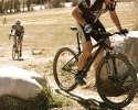 Bo Pihl hammers up a climb on his singlespeed as Courtney Gregory is fast approaching. by Karen Jarchow