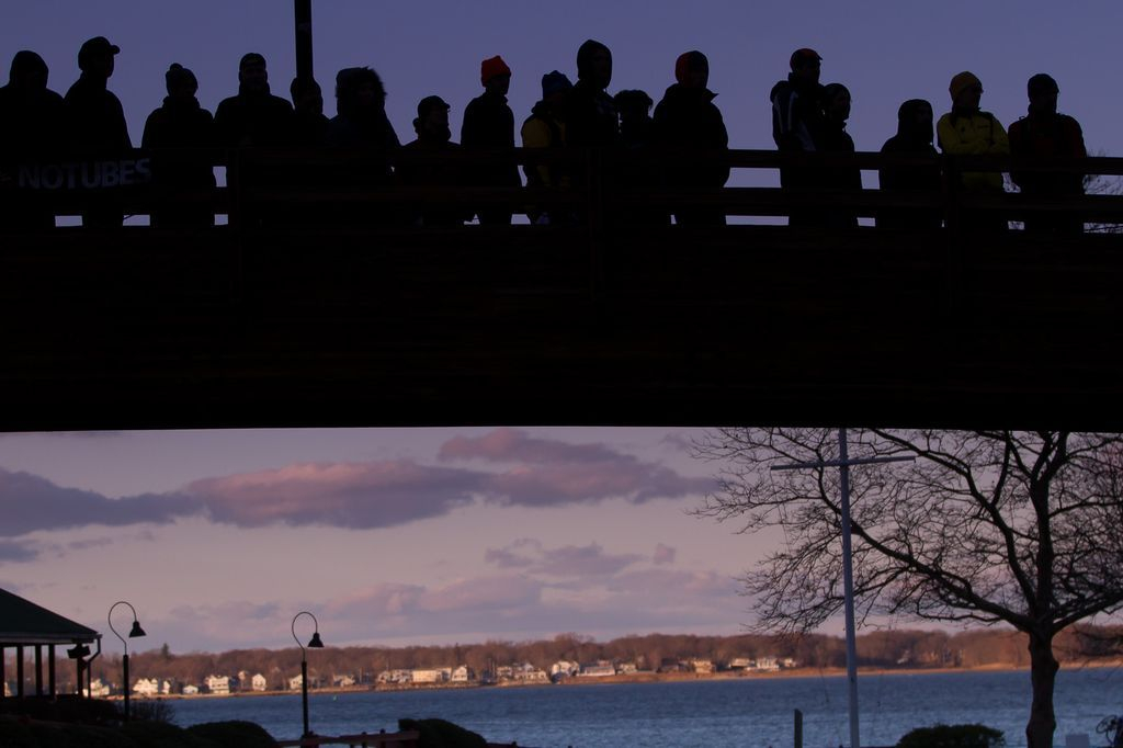 Silhouetted spectators watch the race from the bridge overlooking the finish line. © Todd Prekaski