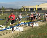 Riders hit the barriers en masse at Campus Cross. © Kenneth Hill, Light and Shadow Photography