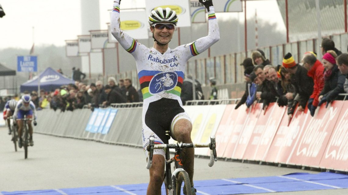 A victorious Vos puts her arms up as Nash sprints behind. © Bart Hazen/Cyclocross Magazine