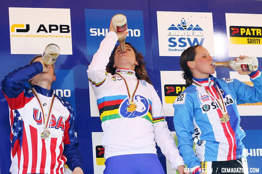 The women\'s podium celebrates with a drink of bubbly