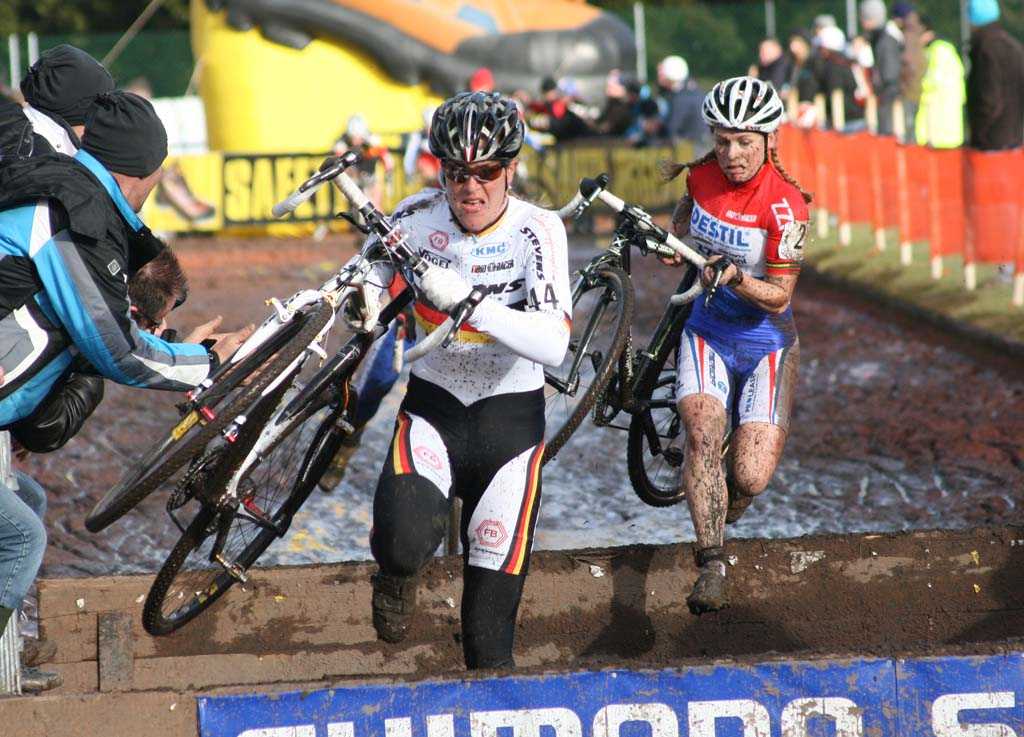 Kupfernagel (l) and Van Den Brand going over the barriers in the mud. ? Bart Hazen