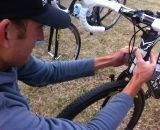 Trebon putting a Pioneer S-Mustache sticker on his head tube.