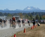 Three Fingers Mountain looms large behind the Men' Elite field as they start their race - credit Kenton Berg