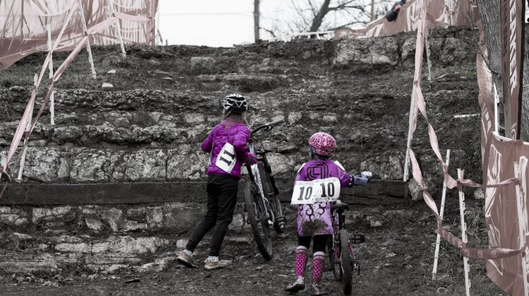 Gretchen Wayman and Mckenna Wilkins, both in Purple and from Texas, trying to figure out how to scale the limestone wall with their heavy bikes. © Cyclocross Magazine
