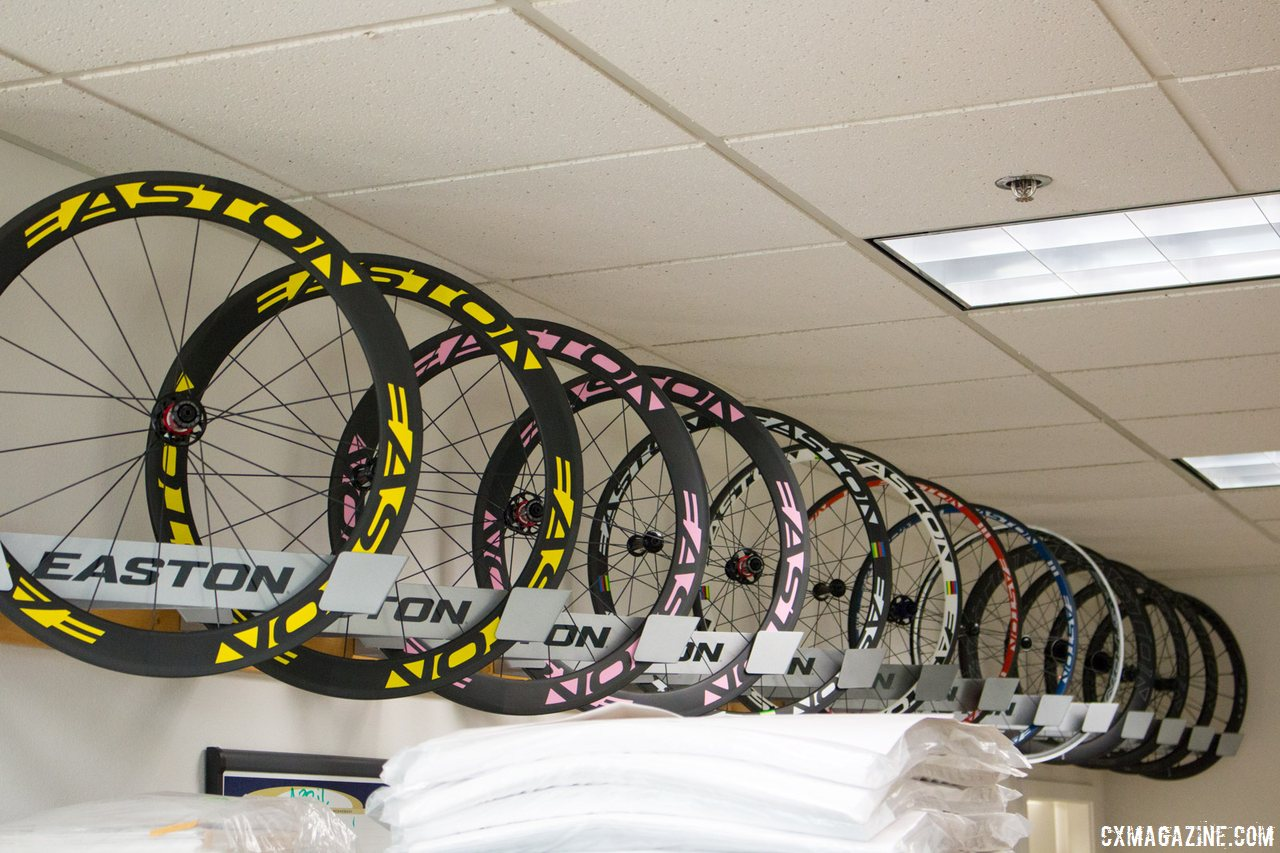 easton-proudly-display-some-of-the-wheels-from-its-most-famous-victories-including-cadel-evans-tour-de-france-victory-wheels-yellow-and-gilberts-world-championship-wheels-behind-the-pink-cyclocross-magazine