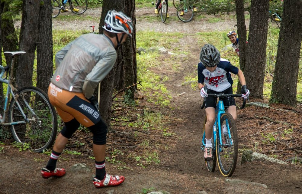 """Cyclocross legend Sven Nys regularly trains his ability to ride very steep climbs. In that tradition, Camp Director Geoff Proctor incorporates a """"Sven Hill (Helling)"""" Competition at every camp. Here, Cyclocross Network's Alex Morton lays down the power during the 2015 competition with encouragement from Assistant Coach Scott Herzig. © Tom Robertson"""