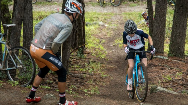 "Cyclocross legend Sven Nys regularly trains his ability to ride very steep climbs. In that tradition, Camp Director Geoff Proctor incorporates a ""Sven Hill (Helling)"" Competition at every camp. Here, Cyclocross Network's Alex Morton lays down the power during the 2015 competition with encouragement from Assistant Coach Scott Herzig. © Tom Robertson"