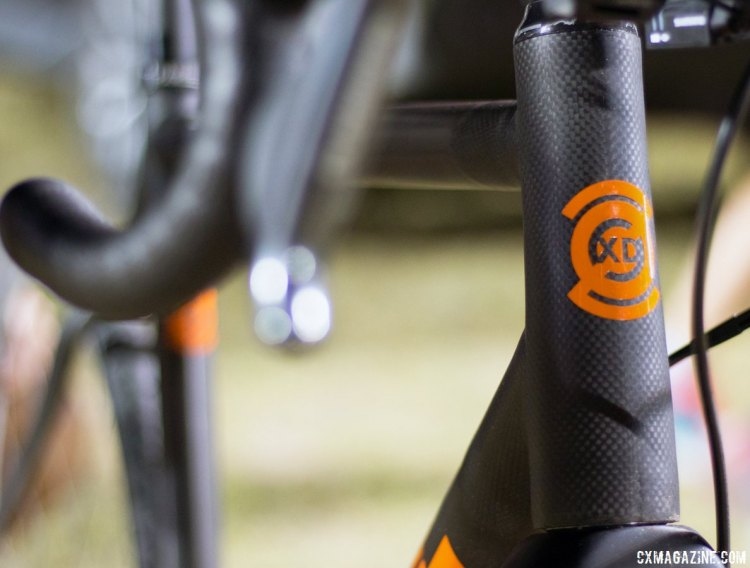"The headbadge of the Parlee Z-Zero XD is painted in ""Lambo Orange,"" and sits over the waxed surface of the bare carbon frame. © Cyclocross Magazine"
