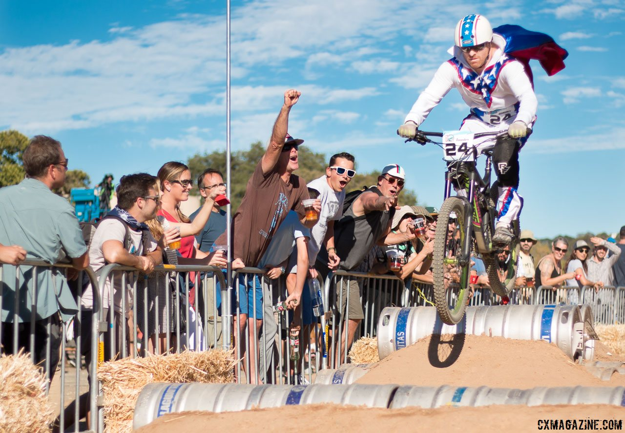 evil-knielvel-gets-big-air-entertains-fans-over-the-beer-kegs-2015-clifbar-cykel-scramble-a-yee-cyclocross-magazine
