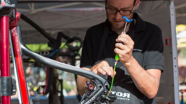 Wolfgang Turainsky tapping out the bubbles, and bleeding the system in just a few minutes. The Uno hydraulic shifting component group from Rotor. © Cyclocross Magazine