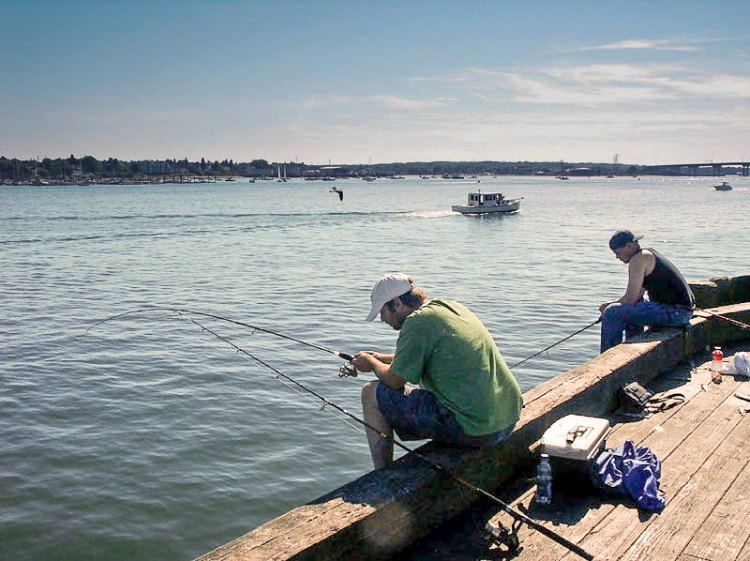Side-by-side, staring into the water or out to sea makes fishing a common guy's bonding activity. photo: Robert Pos