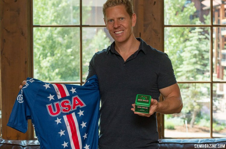 Olympian Sky Christopherson discovered Bag Balm on his own, and used it in training for the Olympics and has converted some women cyclings on the Team USA track team into believers. He's shown here with an autographed Team USA jersey from the women's team that the company was giving away. Press Camp 2017. © Cyclocross Magazine