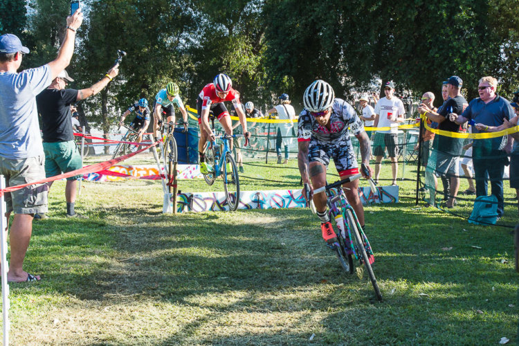 Lead group bunny hops the barriers in front of the beer garden. WSCXGP Day 2. photo: Peloton Sports