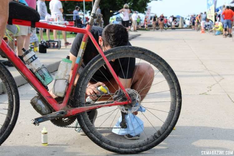 Chain lube was a must-have at the checkpoints. A pit crew member lubes his rider's bike up at Checkpoint 1. 2018 Dirty Kanza 200. © Z. Schuster / Cyclocross Magazine