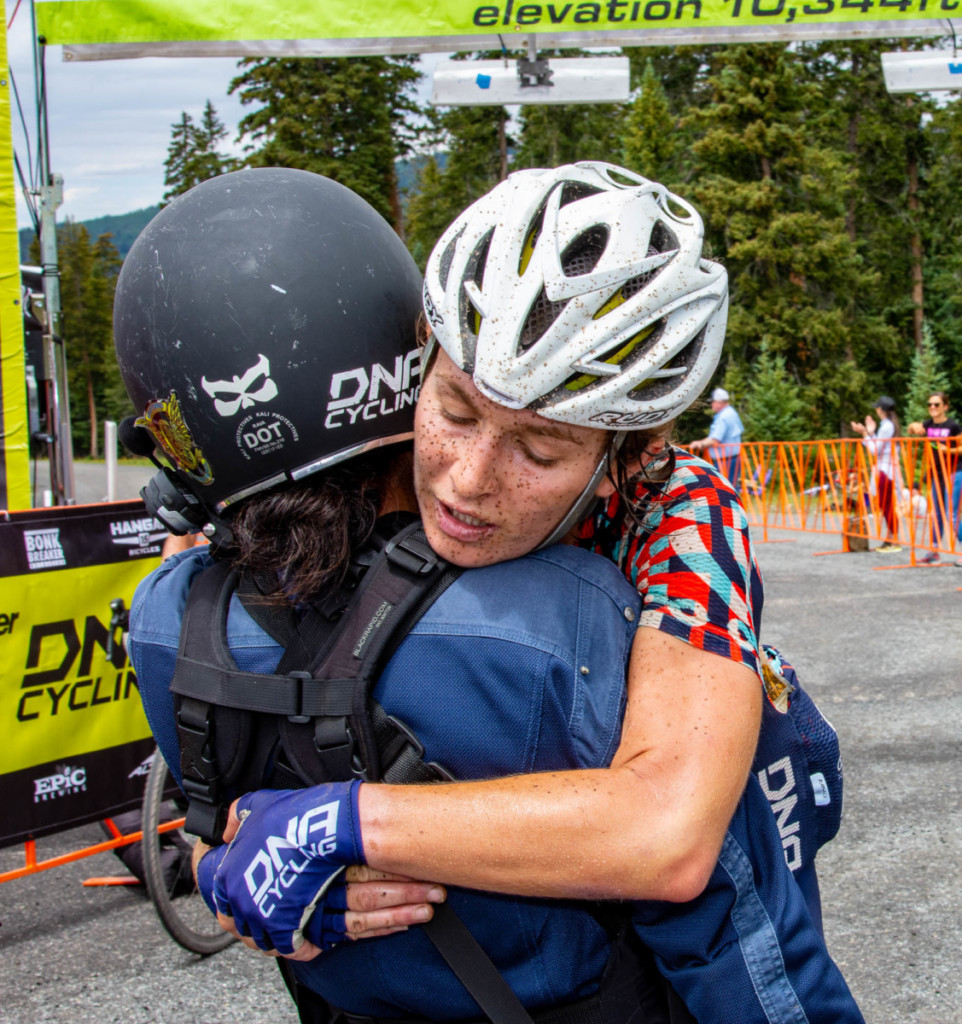 Catherine Fegan-Kim, co-owner of the DNA Cycling Women's Team, hugs Women's Open winner Lauren DeCrescenzo just after the finish line at Eagle Point Resort. 2018 Crusher in the Tusher. photo: Steven Sheffield