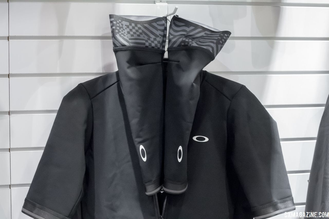 "This unique convertible thermal ""jacket"" pairs a water-resistant, fleece-backed jersey with articulated arm warmers of the same fabric. Oakley's new road cycling kits. 2018 Interbike. © Cyclocross Magazine"