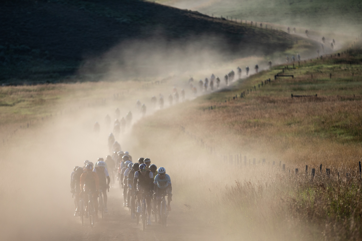 The field rolls down a dusty gravel road. 2019 SBT GRVL gravel race. © Wil Matthews