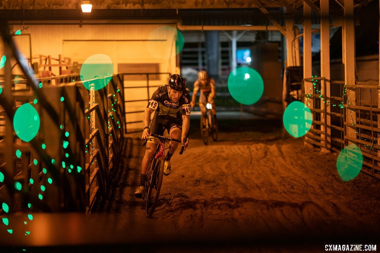 Steve Chainel passes through one of the barns during Friday night's race. 2019 Jingle Cross Weekend. © Drew Coleman