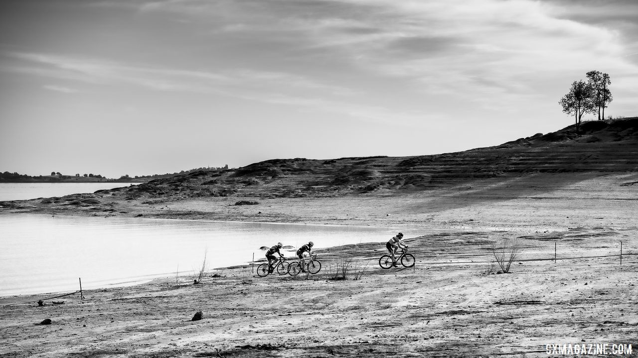 The Mens A podium (Jonathan Baker, Nathan Barton, and Tim Bolton) race along eht edge of Folsom Lake 2019 Sacramento CX Granite Beach, California. © Jeff Vander Stucken