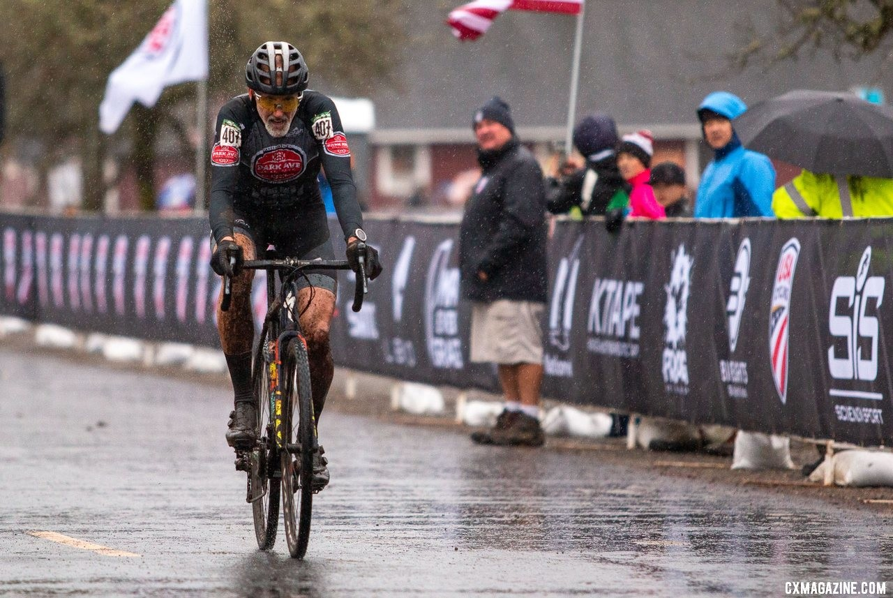Andy August coasts across the finish after a rainy battle with Todd Cassan. Masters Men 55-59. 2019 Cyclocross National Championships, Lakewood, WA. © A. Yee / Cyclocross Magazine